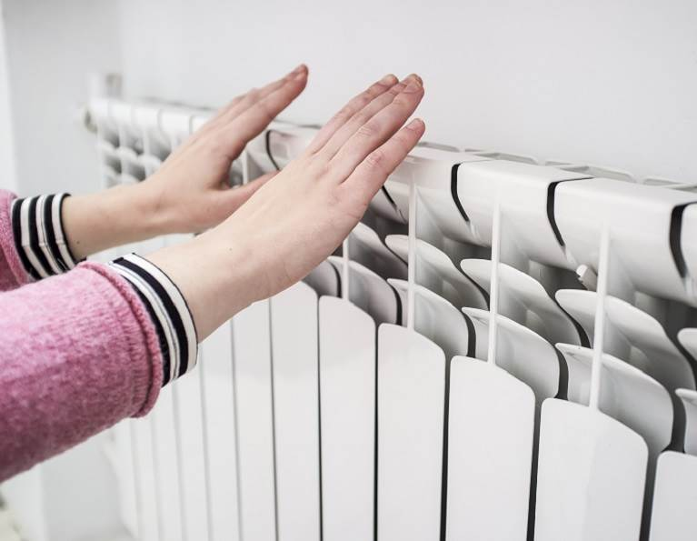 Woman warming her hands on a heating unit representing adhesives for the HVAC industry.